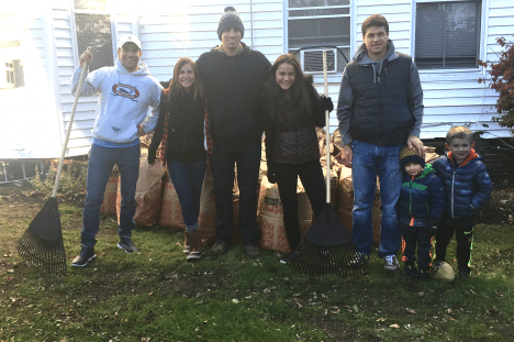 OFFICE HELPS RAKE LEAVES FOR CARITAS COMMUNITIES